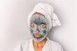 Leinwandbild Motiv Korean beauty face mask foam charcoal bubbles at home self-care treatment asian girl removing dead skin cells with chemical peel face sheet in bathroom.