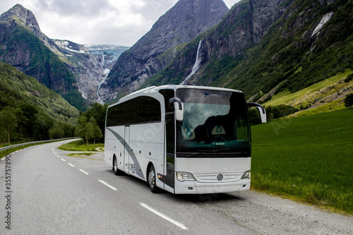 Fototapeta Trip to Norway. Blue ice tongue of Jostedal glacier melts from the giant rocky mountains into the green valley with a lot of waterfalls. Big white tourist bus rides on the road.  obraz