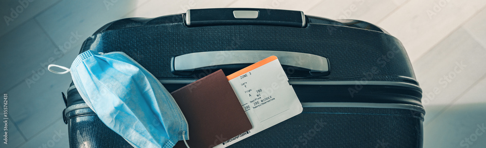 Fototapeta COVID-19 travel restriction due to corona virus mask wearing obligatory in airport and airplane flights to Europe, Asia. Passport, ticket and suitcase ready for holidays. Panoramic banner.