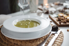 Green Soup In A White Plate On...