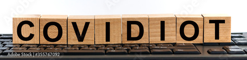 Fotografía COVIDIOT word made with building blocks on keyboard background