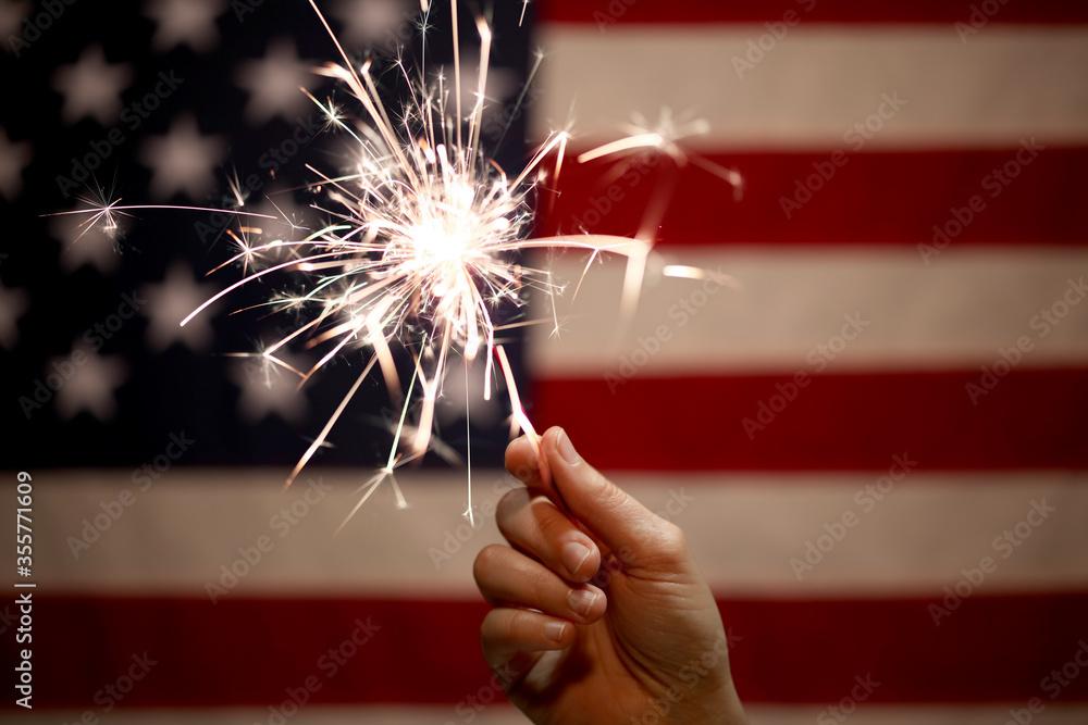 Fototapeta Hand holding lit sparkler in front of the American Flag for 4th of July celebration