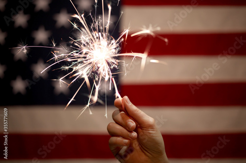 Hand holding lit sparkler in front of the American Flag for 4th of July celebration - 355771609