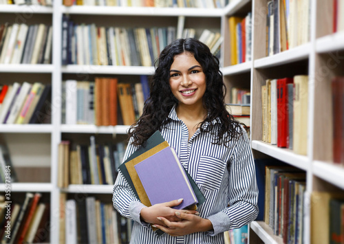 Tableau sur Toile Smiling latina girl holding textbooks at library