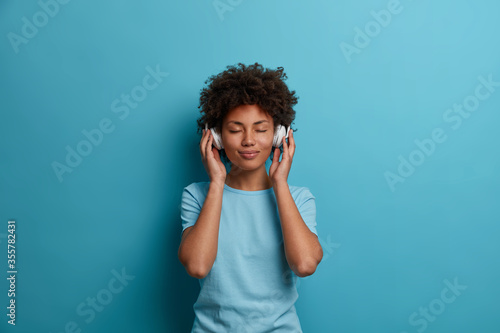 Obraz Satisfied curly young Afro American woman has carefree happy mood, closes eyes and listens music in headphones, wears casual blue t shirt, poses indoor. People, leisue, entertainment concept - fototapety do salonu