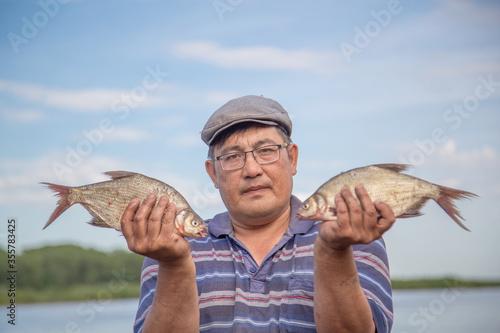 Fototapeta male fisherman in glasses holds a caught fish