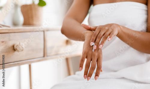 Fototapeta Skin nutrition concept. Unrecognizable black woman applying moisturizing cream to her hands obraz