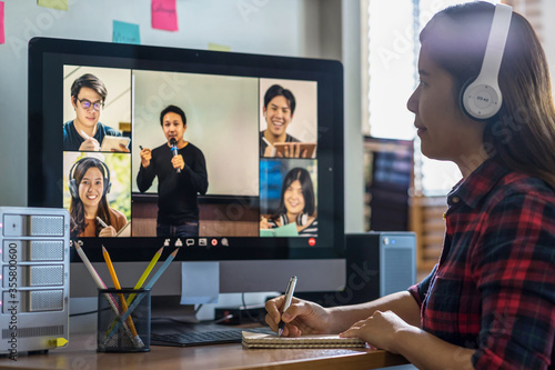 Photo Closeup Asian woman hand writing lecture when online learning via video conferen