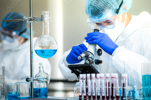 Foto Scientist or researcher hand in blue gloves holding flu, measles, coronavirus, covid-19 vaccine disease preparing for human clinical trials vaccination shot, medicine and drug concept