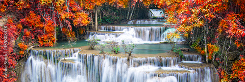 Beauty in nature, beautiful waterfall flowing of water with turquoise color of water in colorful autumn forest at fall season