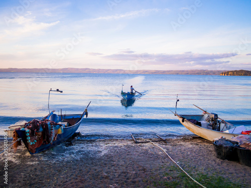 Fotografie, Tablou Fisherman with traditional boat returns to the coast after a fishing trip, Bolse