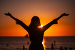 Woman raising arms to sunset