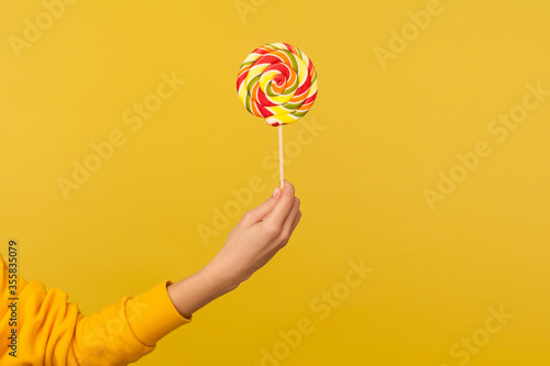 Fototapeta Closeup of hand holding appetizing round rainbow candy on stick, big lollipop in arm, confectionery advertising, glucose sweet foods, sugary dessert. indoor studio shot isolated on yellow background obraz
