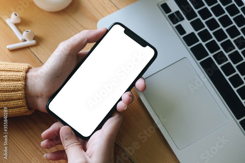 Fototapeta Asian business woman holding and using smart phone with white blank empty screen