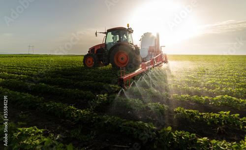 Fotografía Tractor spraying soy field in sunset.