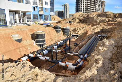 Laying heating pipes in trench at construction site Fototapet
