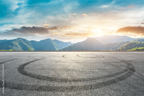 Cuadros en Lienzo Empty race track road and green mountain nature scenery at sunset