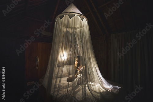 Photo Romantic evening for woman in dark bedroom with lamp light