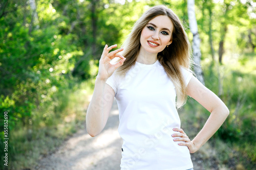 Photo Portrait of a pretty positive smiling woman showing okay sign and over white background, close up portrait, everything is ok, allright
