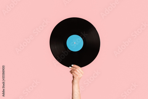Tablou Canvas Girl hand showing retro vinyl gramophone record on pink background, closeup