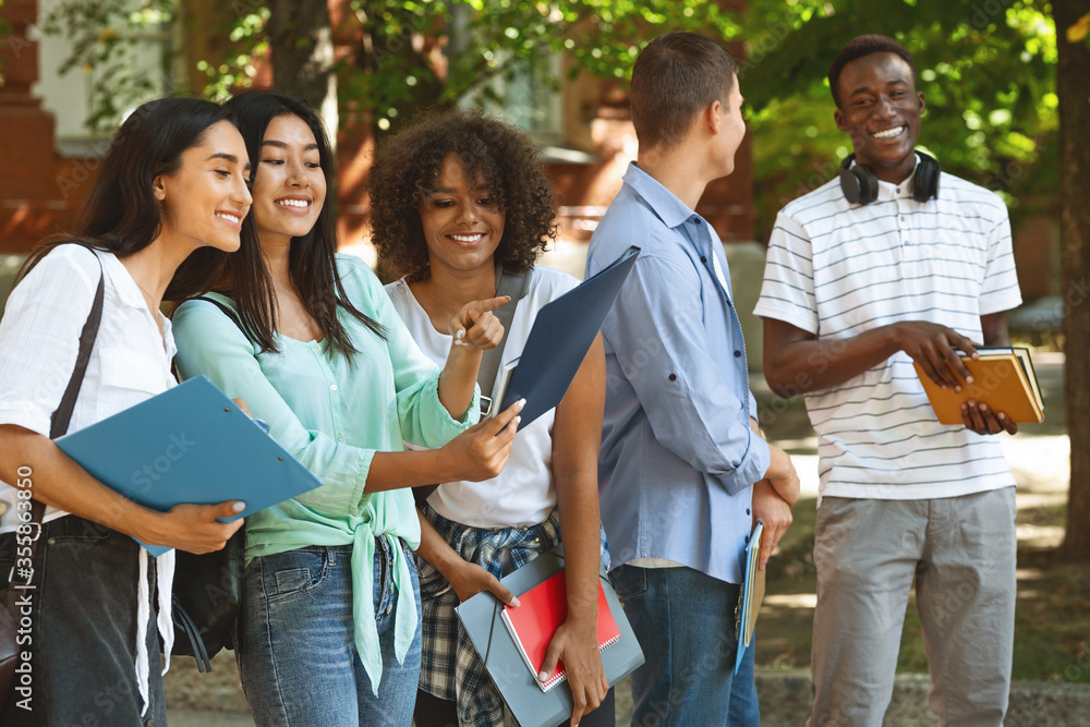 Fototapeta Cheerful Female College Students Checking Schedule Of Classes While Standing Outdoors