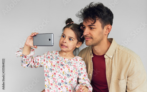Studio image of a young father and his pretty little daughter making a grimace and taking selfie on smart phone against grey background Canvas Print