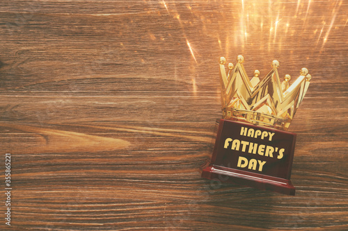 Fototapeta Father's day concept with crown trophy over wooden background. top view, flat lay obraz