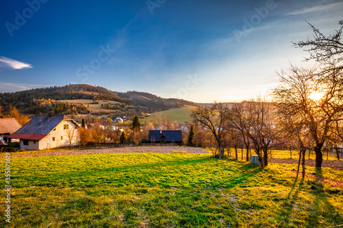 Rural landscape at sunset. Country houses with gardens in a village in the Kysuce region of northwestern Slovakia, Europe.