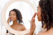 Leinwandbild Motiv Face Care. Young Black Woman Applying Spf Protection Cream On Skin