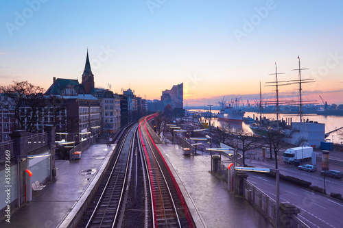 Fototapeta Landungsbrucken station in Hamburg, Germany on a sunrise, early in the morning, with tracer of rear lights of passing train