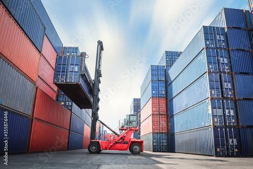 Obraz na plátně Container Ship Loading of Import/Export Freight Transportation Industry, Transport Crane Forklift is Lifting Box Containers at Port Cargo Shipping Dock Yard