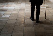 Old Man Legs Walking With Walking Stick On Stone Tiles