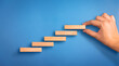 Business person arranging the wooden block steps. Concept of business growth and success. Success steps concept