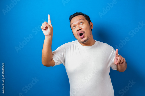 Fotomural Portrait of a funny fat Asian man in white t-shirt smiling and dancing happily,