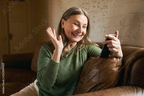 Foto Portrait of beautiful cheerful grandmother having excited look waving hand while