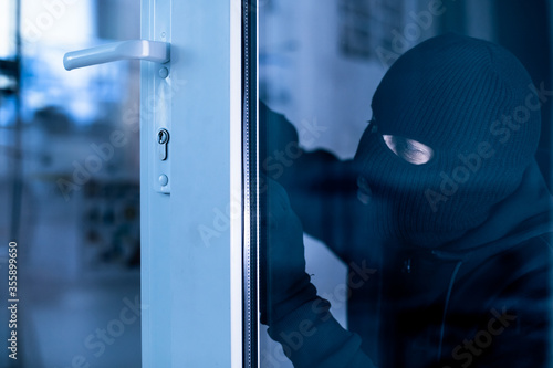 Robber in black balaclava cracking door with metal picklock Wallpaper Mural