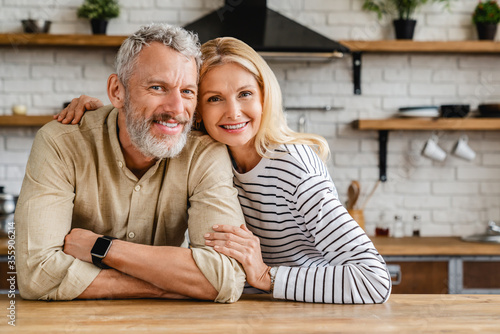 Fotografie, Tablou Portrait of middle aged couple hugging while standing together in kitchen at hom