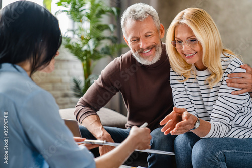 Fotografia, Obraz Estate agent or financial adviser showing terms of contract to happy couple on n