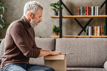 Middle Aged Man Opening Delivery Box At Home