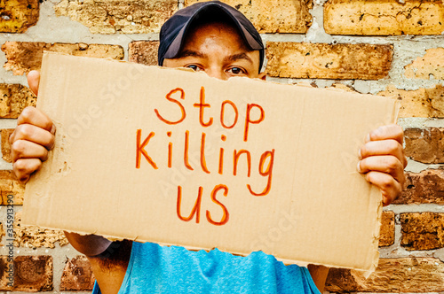 A black man is holding up a sign that says Stop killing us in protest to polic Tapéta, Fotótapéta