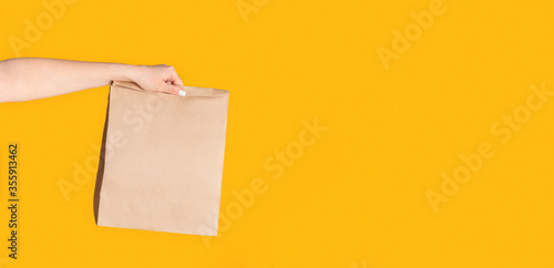 Cuadros en Lienzo Millennial woman holding paper bag with takeaway food on orange background, empt