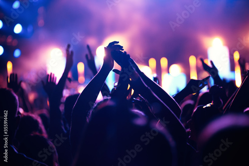 Fotografiet Cheering crowd with hands in air at music festival