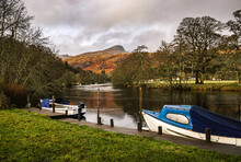 Two Boats Moored At The Private Jetty On River Dochart In Killin, With One Of The Peaks Of The Tarmachan Ridge In The Background.