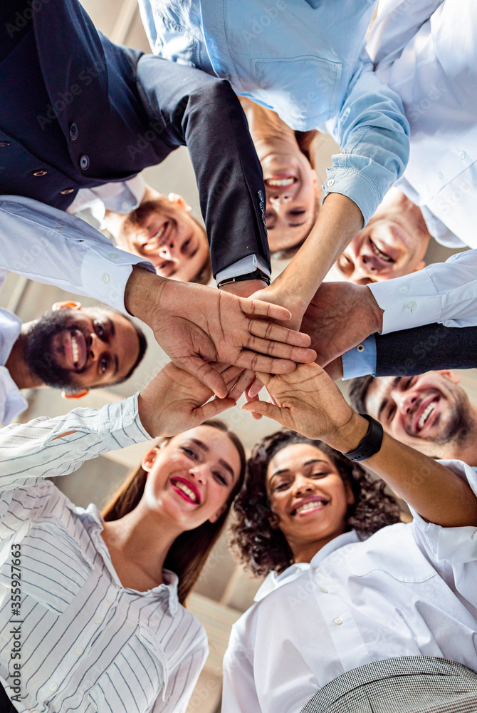 Fototapeta United Business Team Of Colleagues Holding Hands, Bottom View