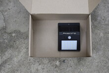 Garden Square Lamp With Solar Panel And Motion Detector In An Open Cardboard Box, Top View.