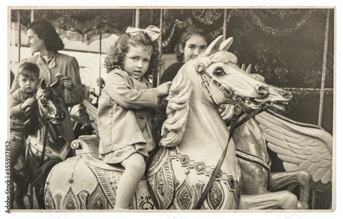 Fototapeta Little girl merry go round carousel Vintage picture