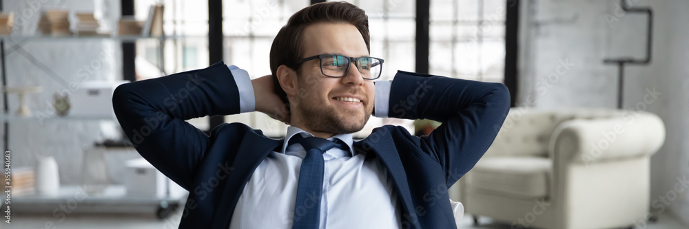 Fototapeta Horizontal panoramic view of smiling young Caucasian businessman look in distance relax at workplace, happy male employer or boss dreaming thinking in office, business vision, success concept