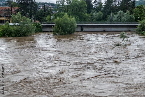 Fotografie, Obraz Climate change: flooding river hits the bridge after a storm in Luino