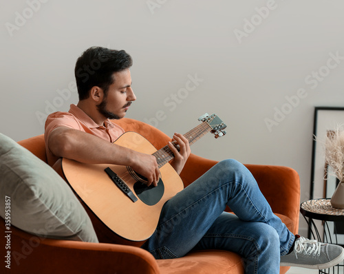 Obraz Handsome young man playing guitar at home - fototapety do salonu