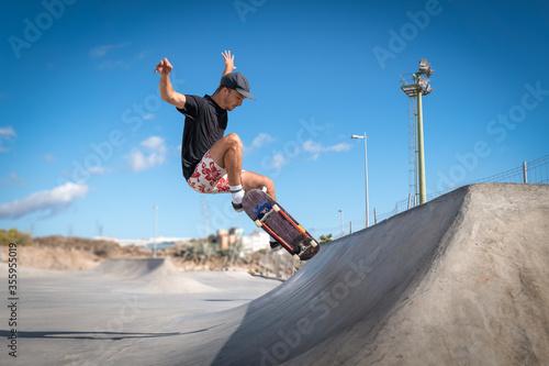 hombre joven hace un salto desde una rampa en un skate park. Canvas Print